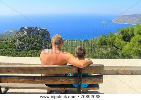 father and son sit on bench