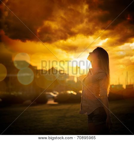 Silhouette of Young Woman at Urban Sunset