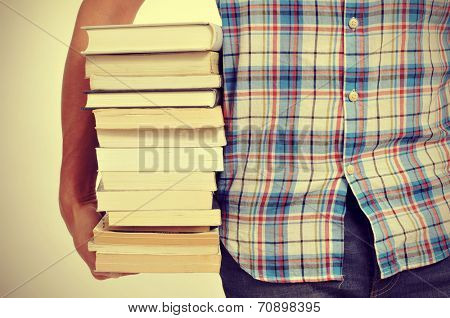 closeup of a young man holding a pile of books, with a filter effect