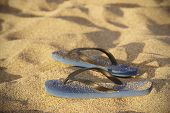 pic of thong  - Blue plastic thongs in the sand. Horizontal