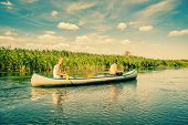 stock photo of canoe boat man  - Canoeing On A Beautiful River At Summertime - JPG
