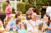 pic of multi-generation  - Multi Generation Family Enjoying Meal In Garden Together - JPG