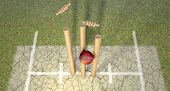 stock photo of cricket ball  - A red leather cricket ball hitting wooden cricket wickets on a grass cricket pitch background - JPG