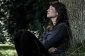 stock photo of pain-tree  - Portrait of young sad woman sitting under the tree - JPG