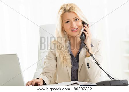 Blonde Businesswoman Phoning In The Office