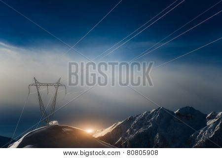 Pylons Covered With Snow In The High Mountains Carry Energy Downstream