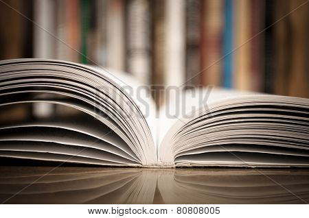 Open book on the wooden table with defocused books in the background