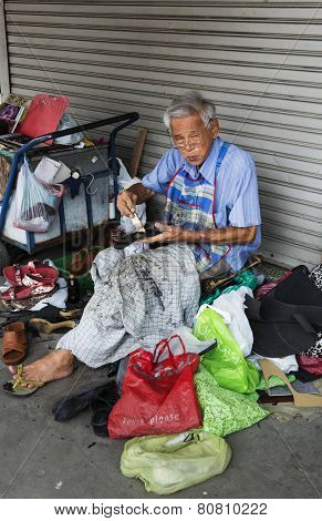 BANGKOK, THAILAND - DECEMBER 25, 2014: Street Photography of shoemaker repairing old shoes.
