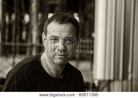 Street photography of smiling 40-year-old man. Sepia toned