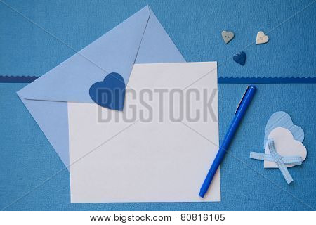 Blue envelope and white blank paper with hand made heart crafts