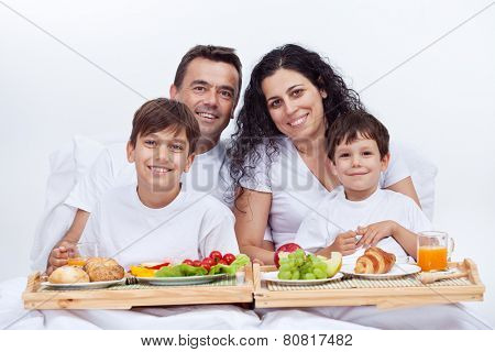 Happy family having breakfast in bed on a bright morning