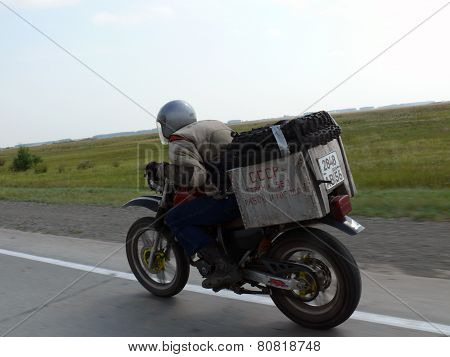 Baikal, Russia - August 13, 2012: The Unknown Man Goes On The Road On A Motorcycle.