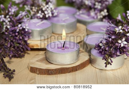 Scented Candles On A Wooden Stand With Lilac Flowers On The Table.