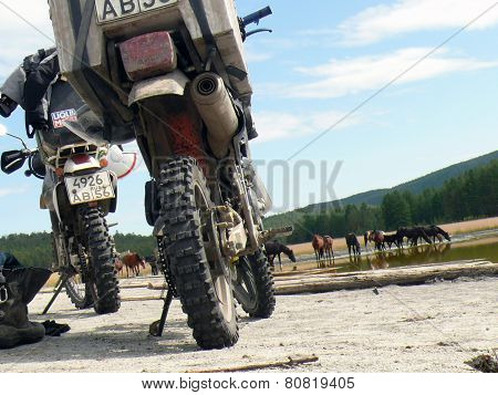 Baikal, Russia - August 13, 2012: The Landscape Of Nature. Motorcycles Are Near The Lake. Horses Dri