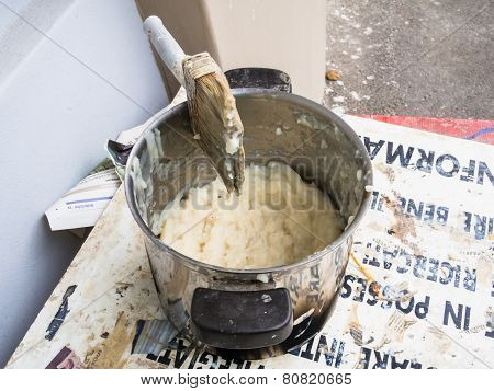 Container of glue for paper mache with brush