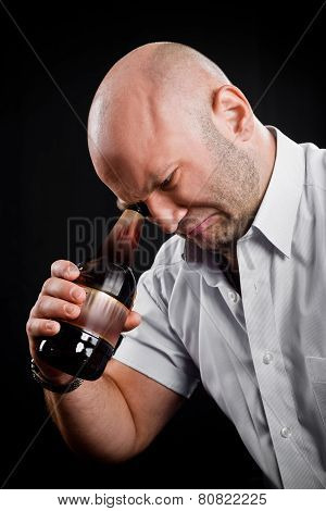 Man Very Emotionally Looks At The Bottom Of The Bottle