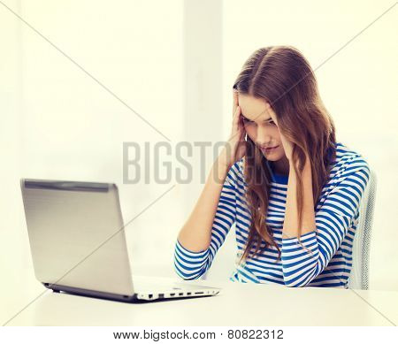 home, technology and internet concept - upset teenage girl with laptop computer at home
