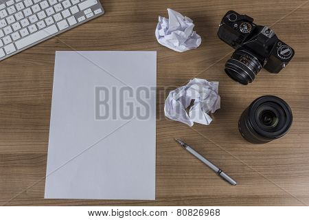 Desktop With Camera And Blank Sheet