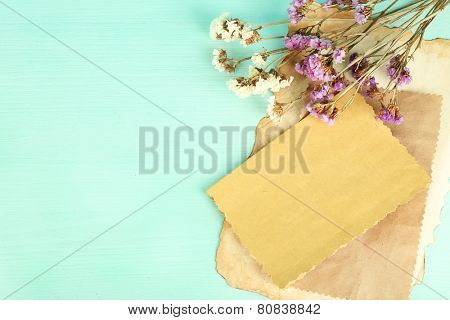 Old card with dry flowers on wooden background