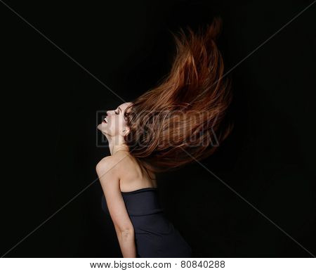 Beautiful dancing young woman with flowing long hair on dark brown background