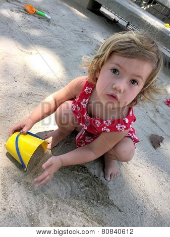 Cute little kid playing with yellow bucket and sand on the playground