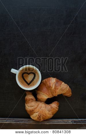 coffee with hearts and croissant at board