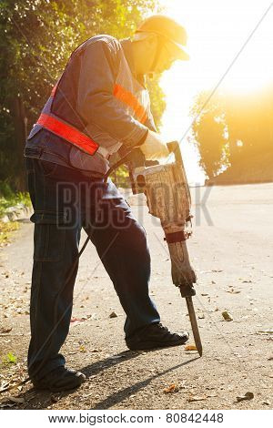 Worker With Pneumatic Hammer Drill Equipment Ready To Breaking Asphalt At Road