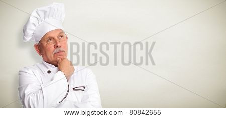 Senior professional chef man over grey wall background