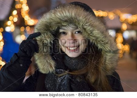Christmas portrait of a laughing girl in a fur hat