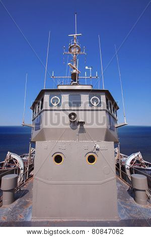 Front View Of Military Ship Bridge Control Room Against Clear Blue Sea And Sky