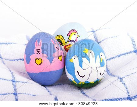 Bright colored hand painted Easter eggs with cute animals on a soft white and blue towel