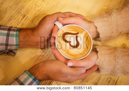 Four Hands Wrapped Around A Cup Of Coffee With Heart Drawing