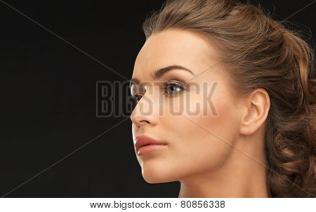 face of beautiful beautiful woman over black background