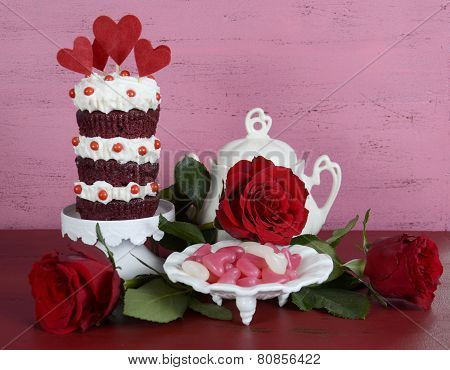 Vintage Style Triple Layer Red Velvet Cupcake On White Cake Stand With Roses And Candy Against A Vin