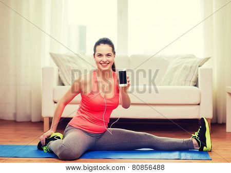 fitness, home, technology and diet concept - smiling teenage girl streching on floor with smartphone and earphones at home