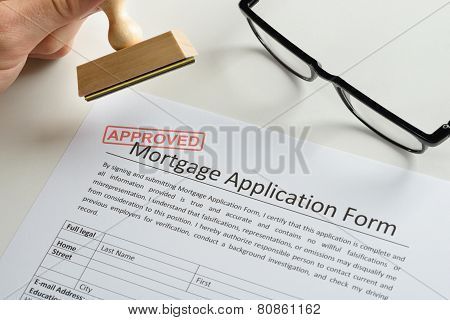 Person Hand With Stamp And Approved Mark On Mortgage Application