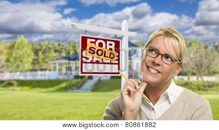 Attractive Young Adult Woman with Pencil in Front of Sold For Sale Real Estate Sign and House.