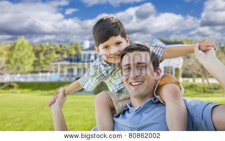 Mixed Race Father and Son Playing Piggyback in Front of Their House.