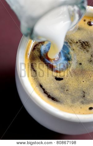 Milk Poured Into Small Cup Of Coffee