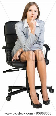 Businesswoman on office chair holding finger to her lips