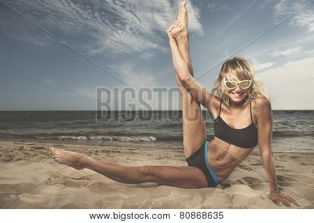 Young woman extends her leg while and doing yoga on beach with the ocean in the background.
