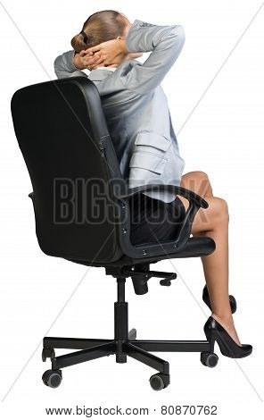 Businesswoman sitting back in chair with hands clasped behind her head