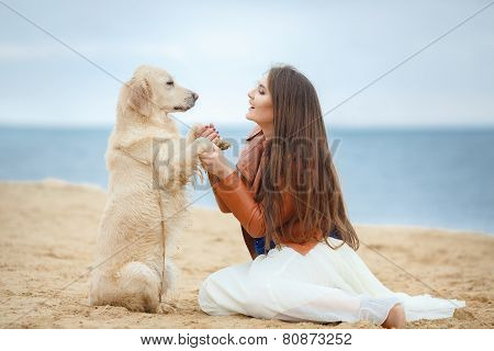 Beautiful young woman playing with dog on the beach