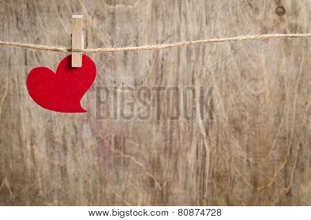 Red Fabric Heart Hanging On The Clothesline. On Old Wood Background.