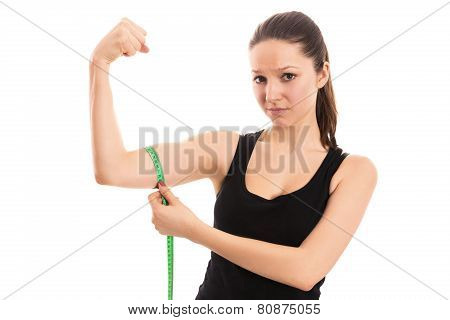 Disappointed woman measuring bicep