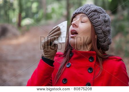 Young woman with a cold or flu sneezing on a white paper handkerchief on a forest wearing a red overcoat, a beanie and gloves during winter