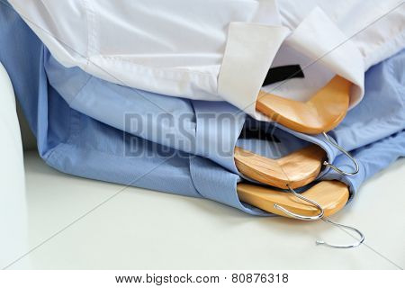 Shirts on hanger, on white armchair background