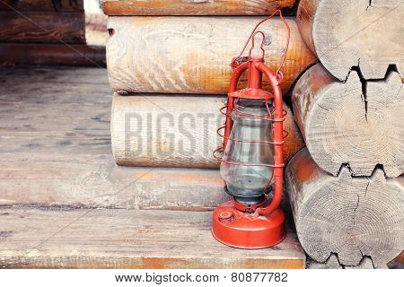 Kerosene lamp on wooden hose background