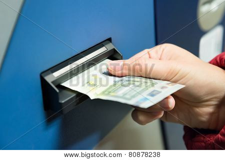 Woman Inserting Cash Into Machine