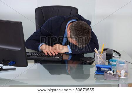 Tired Businessman At Desk